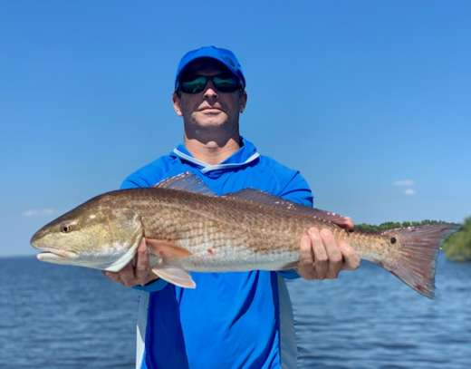 Mr Wynn with a monster Redfish, released unharmed. Nice catch