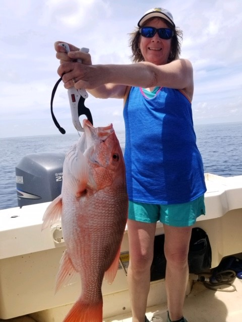 Susan with a monster Red Snapper caught with Hookedup Charters